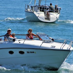Two white luxury boats spending the day in open water with bright sunshine