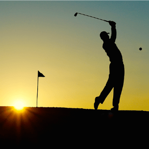 The silhouette of a golfer in late day sunset hitting a ball by a tee