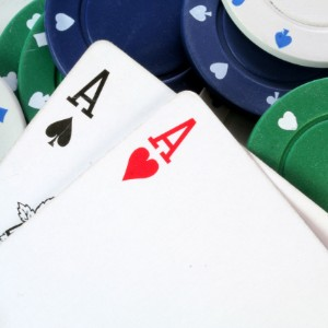 Two playing cards with Aces and white, red and green poker playing chips on a table