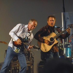 A man in a white shirt playing electric guitar next to a man in a brown shirt playing acoustic guitar