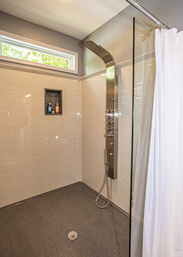 Glass shower with glossy tiles and modern shower head of polished metal. A narrow window offers natural lighting.