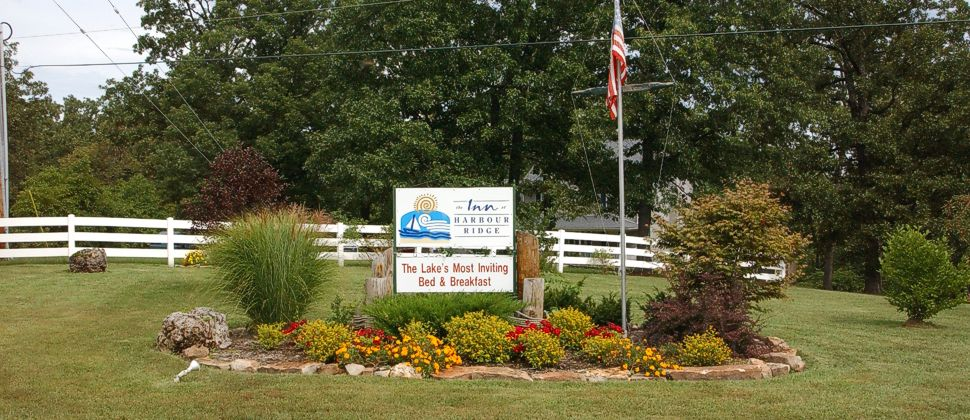 Flowers and bushes in lawn decoration with Inn at Harbour Ridge sign and flagpole