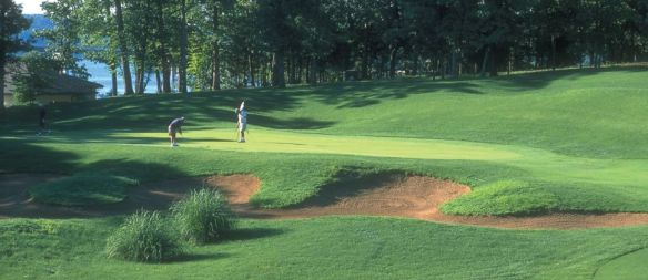 Two men on green golf course with sand trap and green trees in background