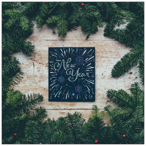 Black poster with text New Year with green pine branches around the border