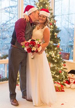 A bride and groom sharing a kiss in front of a Christmas tree. Both are wearing Santa Claus hats and are holding a red and white bouquet.
