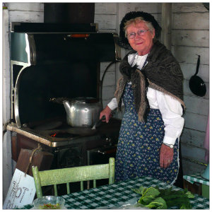 A Mennonite lady standing beside a wood stove with a table of vegetables