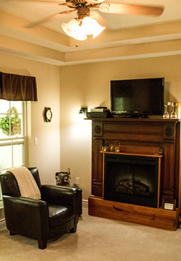 Corner of a cream colored room with wood-framed fireplace, brown leather club chair and ceiling fan