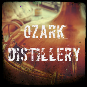 A copper machine used for distilling with text Ozark Distillery - image by martin knife unsplash.com