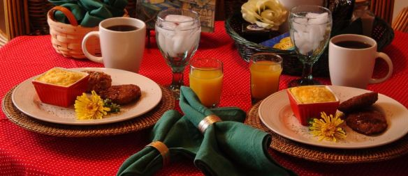 Breakfast place settings with coffee and ornage juice and egg souffle in red ramekins