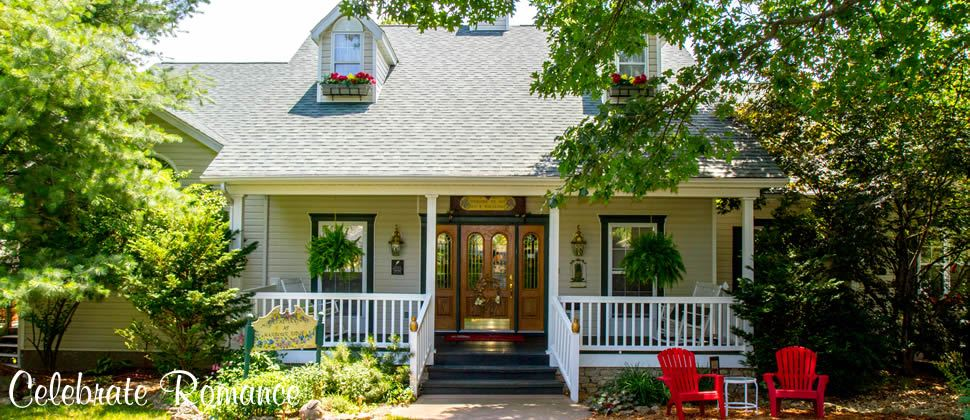 Pretty house with flowers in windowboxes with white porch railing and large wooden doors