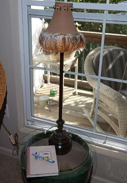 Side table made of large pot with pink lamp set in front of sunny window
