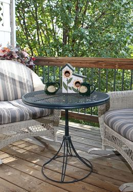 White wicker chairs with green iron table on wooden deck topped with birdhouse and mugs