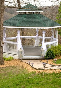 Stone path leading to large white gazebo with green shake roof