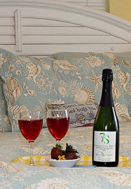 Blue bed with wine bottles and glasses with red wine and strawberries