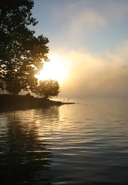 Sun coming up over hazy lake with trees on the shore