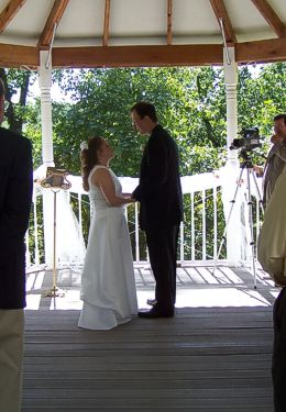 Bride and Groom gazing at one another in sunlit gazebo.