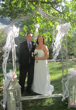 Bride in White dress and groom in back suit standing behind white decked arbor