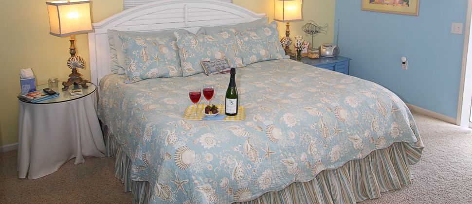 Blue spread on bed with wine glasses and strawberries on yellow plaid tray