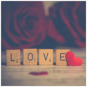 Four brown Scrabble letters spell out LOVE in front of red roses