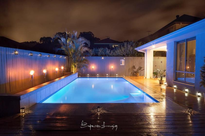 backyard pool with glass fence