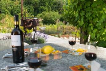 an einem lauen Sommerabend mit einem Glas Wein gemütlich im eigenen Badegarten anstossen