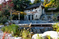 Blick über Schwimmteich zu Rustico mit Pergola Tessin gemütlich mediterraner Garten