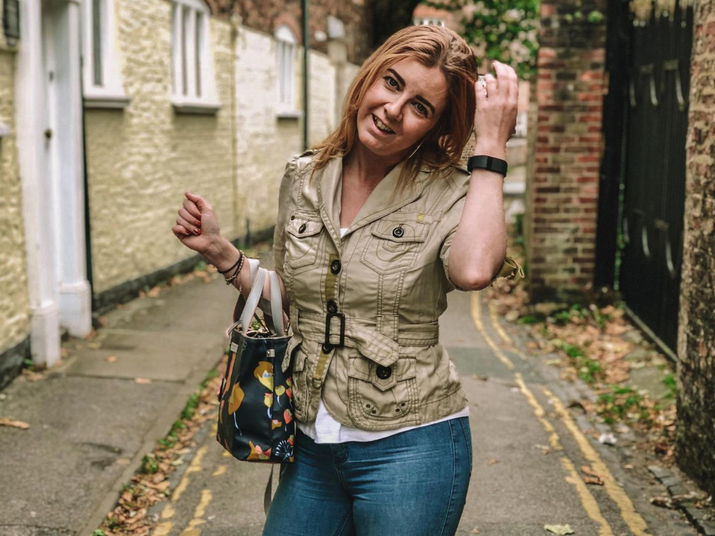 Autumn street scene in York with Emma dressed in a fitted jacket & jeans standing centre smiling