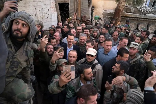 Sur la page Facebook de la présidence syrienne, Bachar Al-Assad pose, le 18 mars 2018, parmi des militaires dans la Ghouta, peu avant la reddition de ce faubourg damascène rebelle.