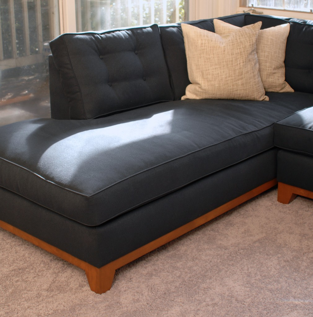 Navy blue sectional sofa and two white pillows