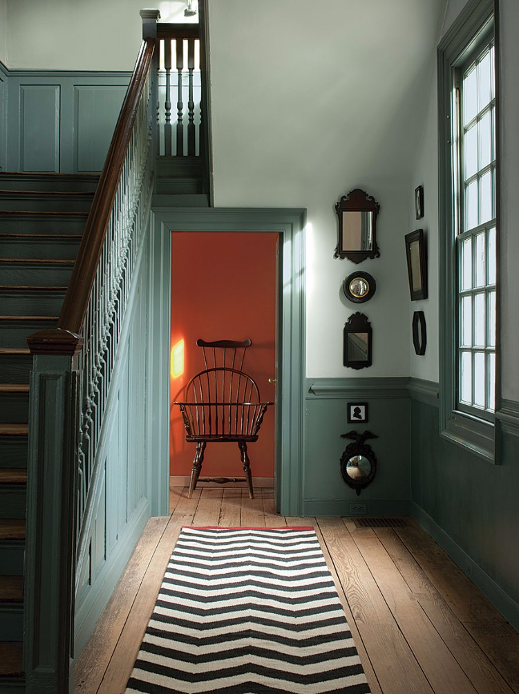 entryway with colorfully painted walls and a black and white rug