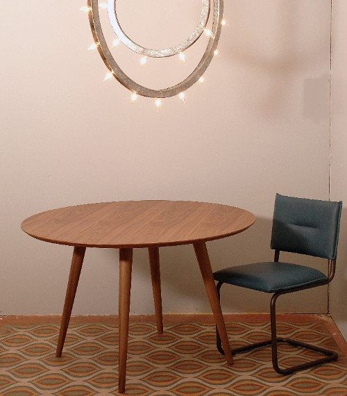 decorative hanging light fixture above a wood table and blue chair