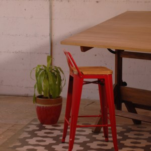 red metal bar stool with a wooden seat at a table