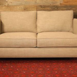 cream colored love seat sofa with metal embellishments
