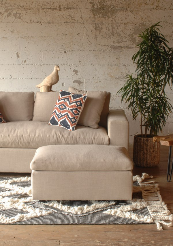 cream colored sofa and ottoman in a living room with furniture and decor