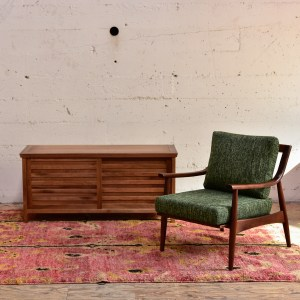 wood media cabinet and green armchair