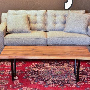 wood and steel coffee table on a red rug