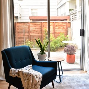 Blue accent chair in room with side table and plants