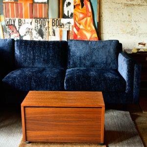 Blue velvet sofa and wood storage chest
