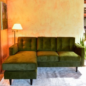 green velvet sofa with chaise in a living room with plants and decor