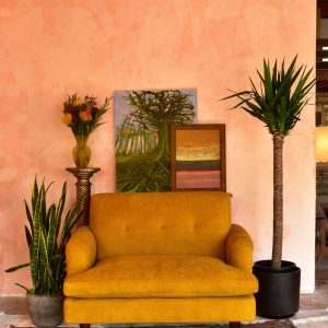 loveseat sofa in a room with art and plants