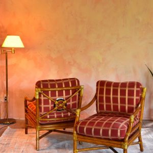 two patterned arm chairs in a living room with a pink wall
