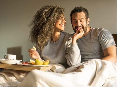Couple of spouses, sitting on their bed, having breakfast, while she gives him fruit in her mouth