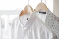 Freshly ironed shirt and blouse hanging on wooden hangers