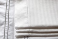 White pillow cases, neatly folded and stacked.