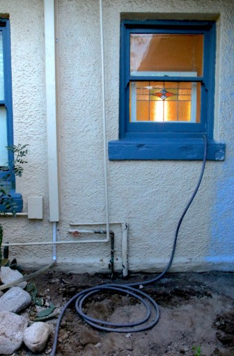 Figure 4. Hose coming out of bathroom wall. Hose is daily moved to a different plant/zone to keep soils healthy, aerobic, and odor-free. Photo credit: Moses Thompson.