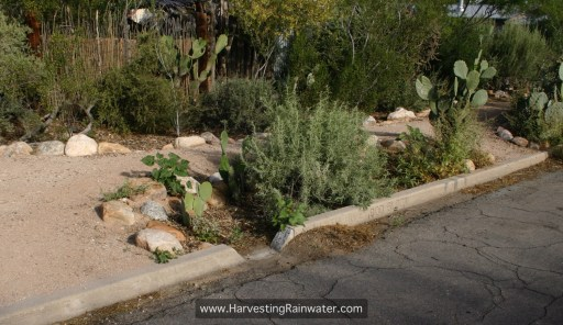 "Fig. 6. Finished curb cut and basin. Gravel and other sediment shoveled from street-curb gutter (on the upstream side of the curb cut) is placed on the downstream side of curb cut to help direct more flow into the basin. See ""Important Elevation and Slope Relationships"" in chapter 8 for how this basin could be improved."