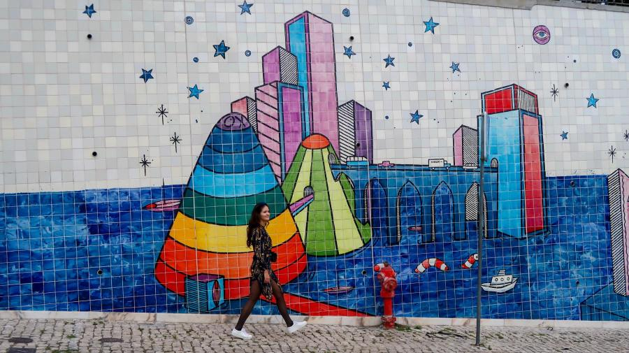 Explorer Melissa at rainbow mural Alfama, Lisbon, Portugal. Do a walking tour through Lisbon to discover this art.