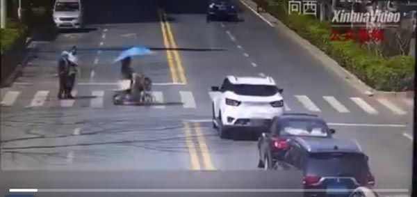All cars stop and wait when a young lady helps an elderly man cross a road in Siyang County, east China's Jiangsu