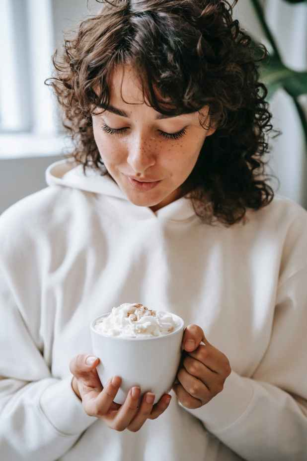 woman blowing on coffee with whipped cream