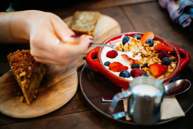 person holding spoon and round red ceramic bowl with pastries